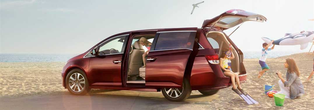 Family playing on the beach by their 2017 Honda Odyssey