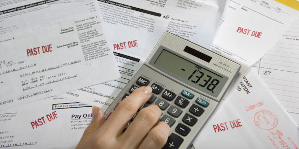 Woman using calculator on desk full of bills and statements, close-up of hand