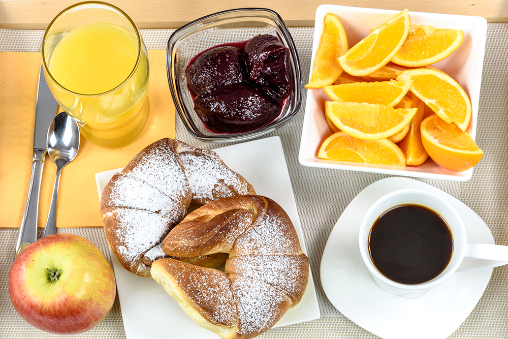 Overhead shot of a breakfast tray with croissants, coffee, oranges, juice, jam, apple and cutlery