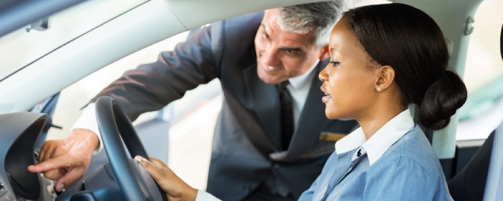 beautiful young african woman buying a car at dealership