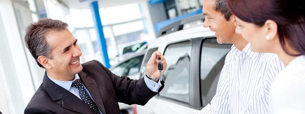dealer handing keys to customers