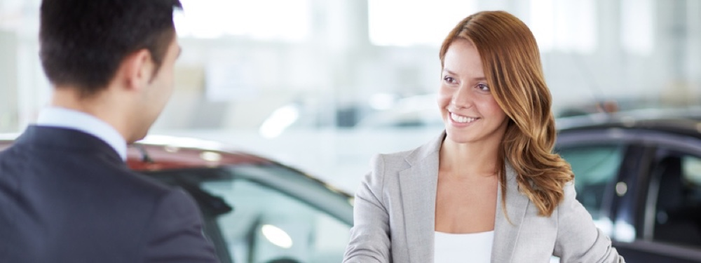 Image of car dealer handshaking with happy female in automobile center