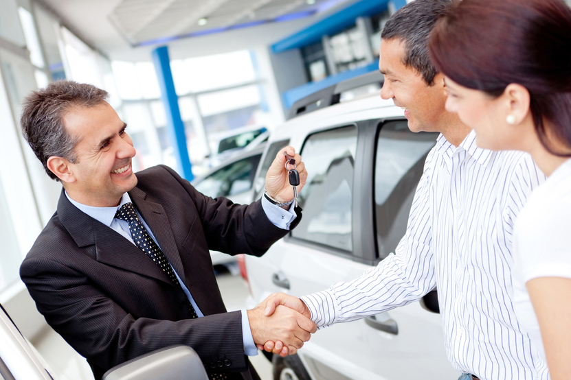 Couple buying a car and salesman handling keys
