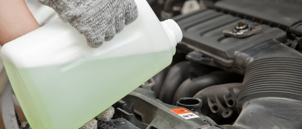 Mechanic adds coolant to engine