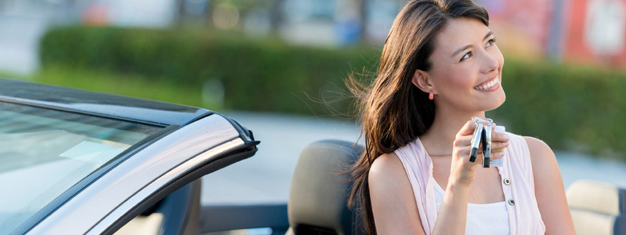 Thoughtful woman holding car keys looking happy