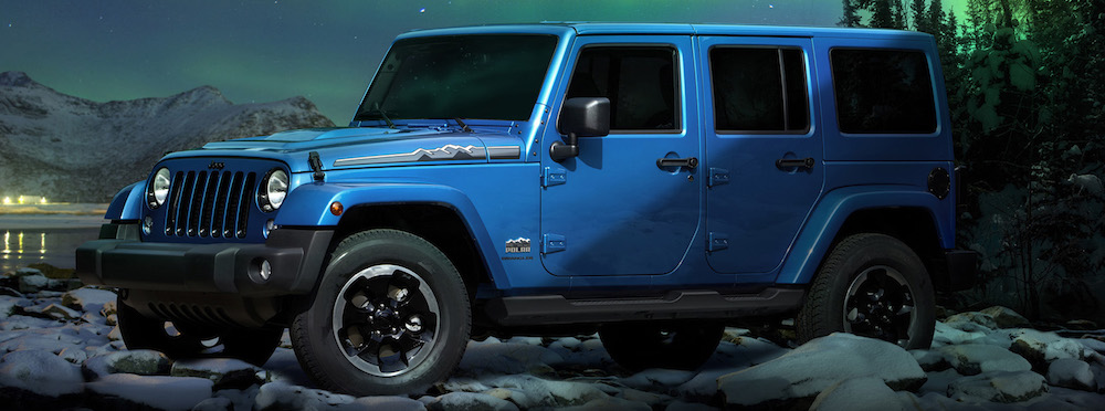 A used 2013 Jeep Wrangler Polar edition is parked in a snowy forest at night.