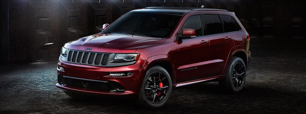 A red 2016 used Jeep Grand Cherokee SRT edition is parked in a dark alley.