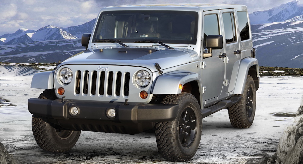 A silver 2012 used Jeep Wrangler Unlimited Arctic edition is parked on a snowy mountain.