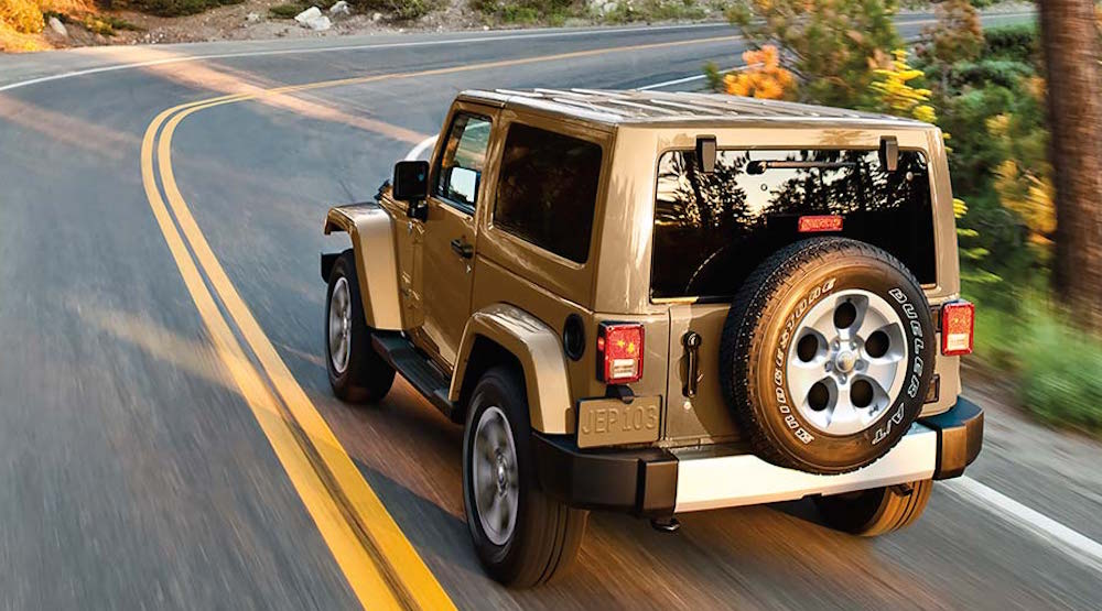 A Gold used Jeep Wrangler for sale with a hard top is driving on a winding Colorado Springs road.