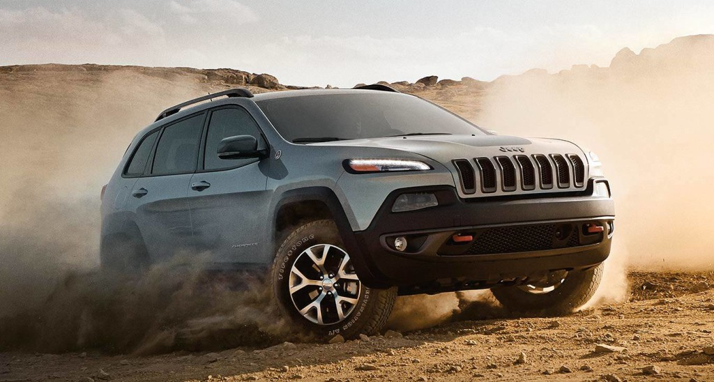 A silver 2016 Jeep Cherokee is kicking up sand on a desert track.