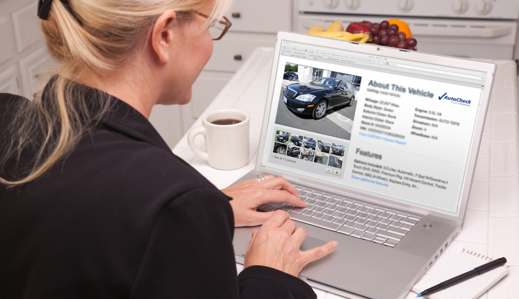 Woman Sitting In Kitchen Using Laptop with Blank Screen.
